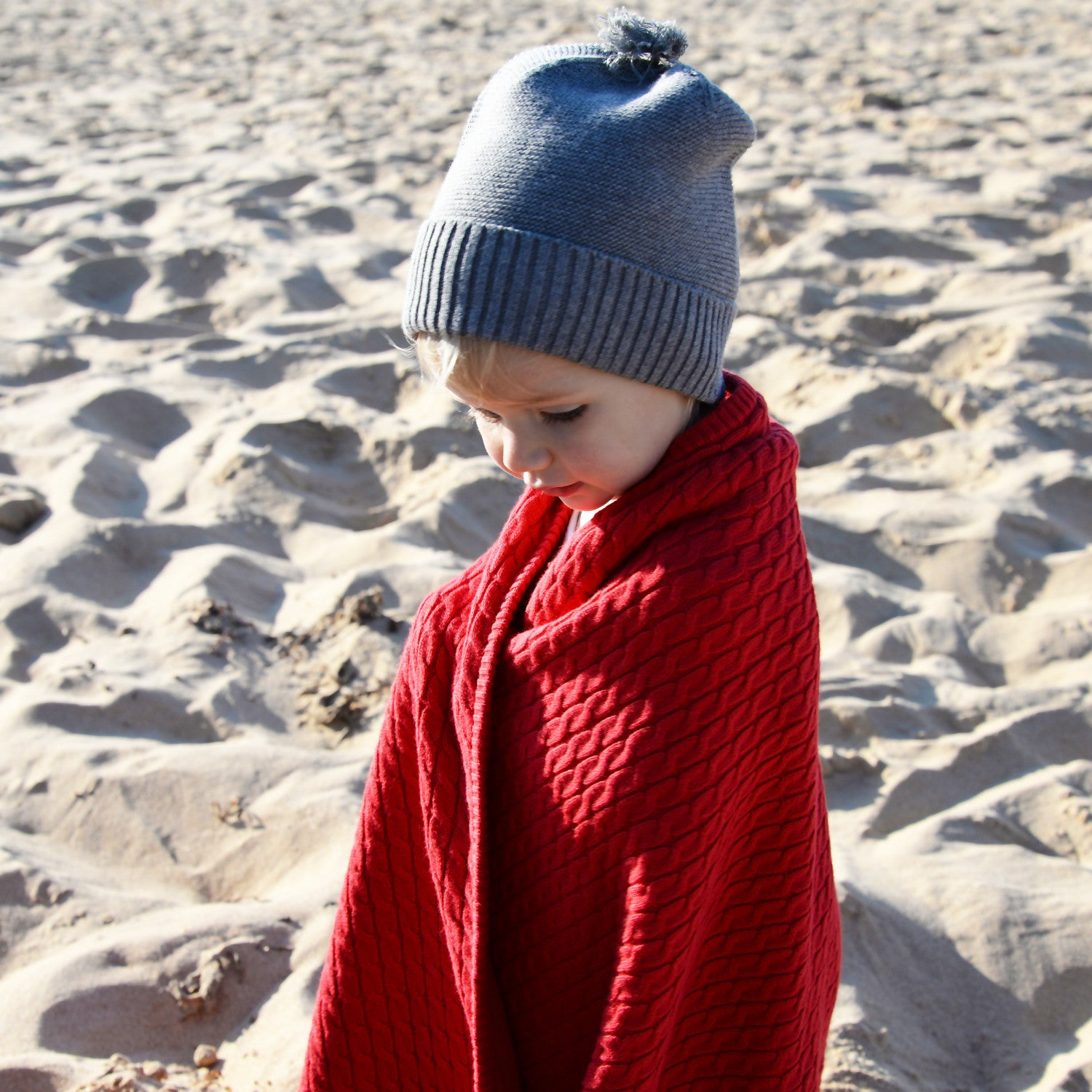 girl on beach in grey beanie and blanket