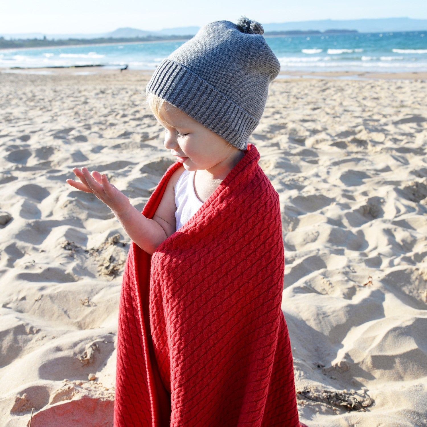 girl on beach with red knit baby blanket