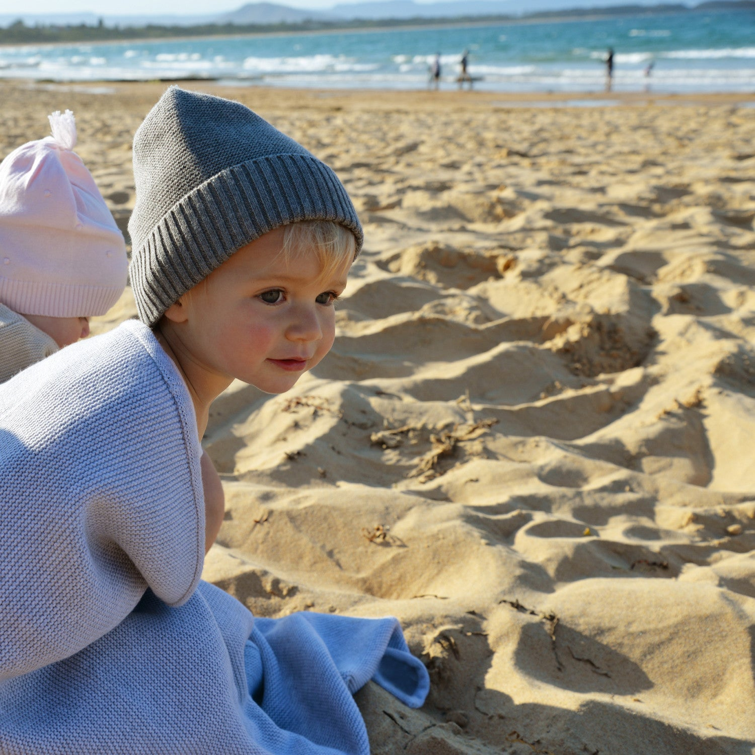 girl on beach in grey marle blanket