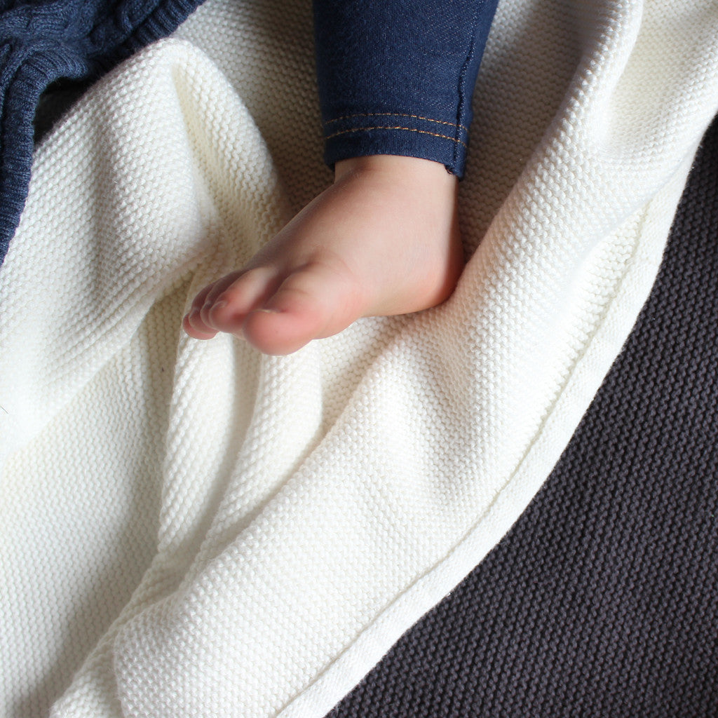 baby feet on white knit blanket