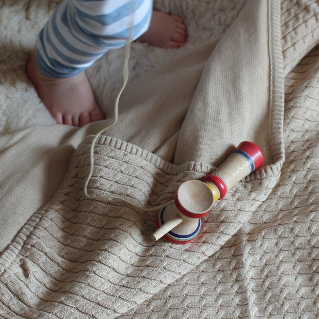 caramel cable knit blanket with baby feet
