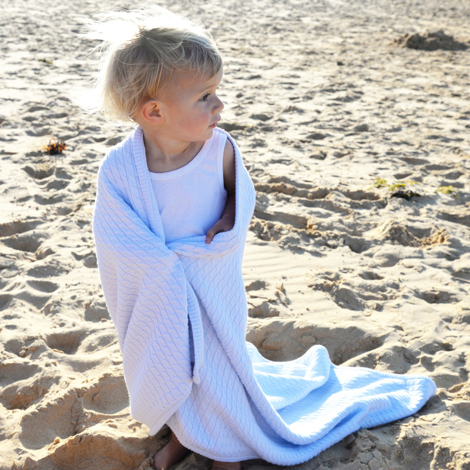 girl on beach with blue knit baby blanket