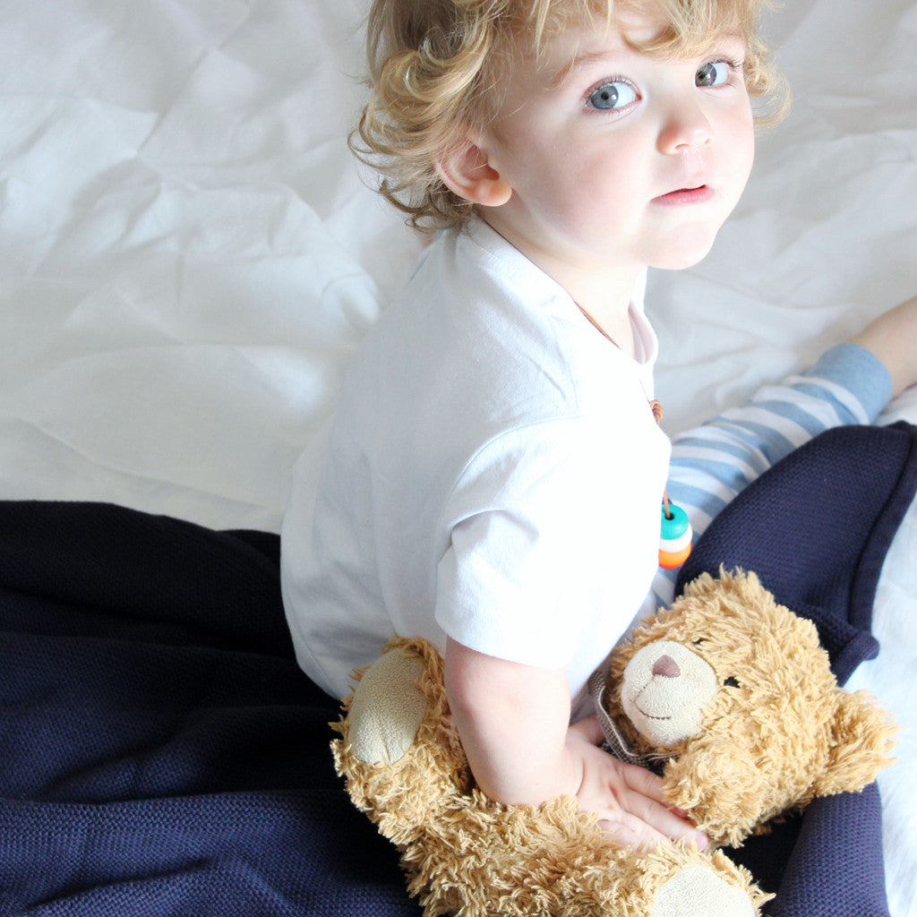 baby and teddy on navy blue blanket
