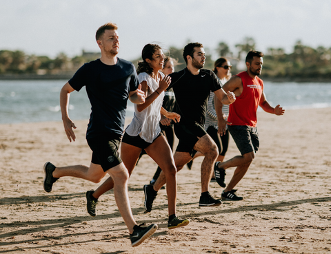 A group of 6 people running on the beach in exercise clothing