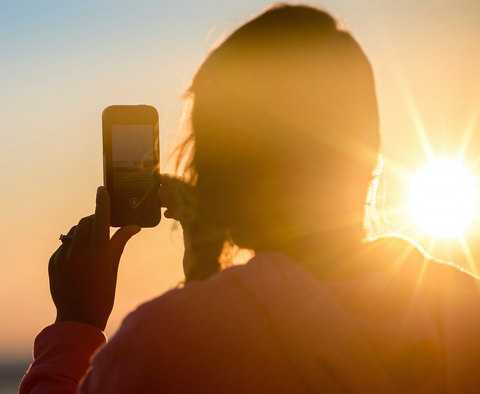 Woman using her phone to take a picture of the sun