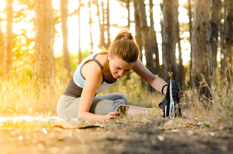 woman stretching while sitting on the ground in the forest, before or after her run