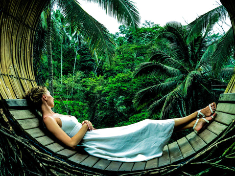 Woman wearing blue dress laying in a wooden hammock looking into the jungle
