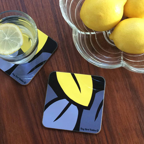 Square drinks mat coaster in grey and yellow Eucalyptus Leaf design, with glass of water and blow of lemons, on dark wood table