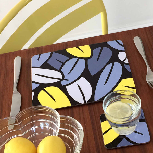 Square drinks mat coaster in grey and yellow Eucalyptus Leaf design, with glass of water and blow of lemons, on dark wood table, with yellow chair in background