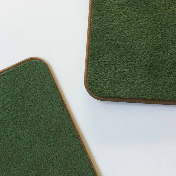 Reverse side of placemats, showing 2 sections of mat with green baize material backing