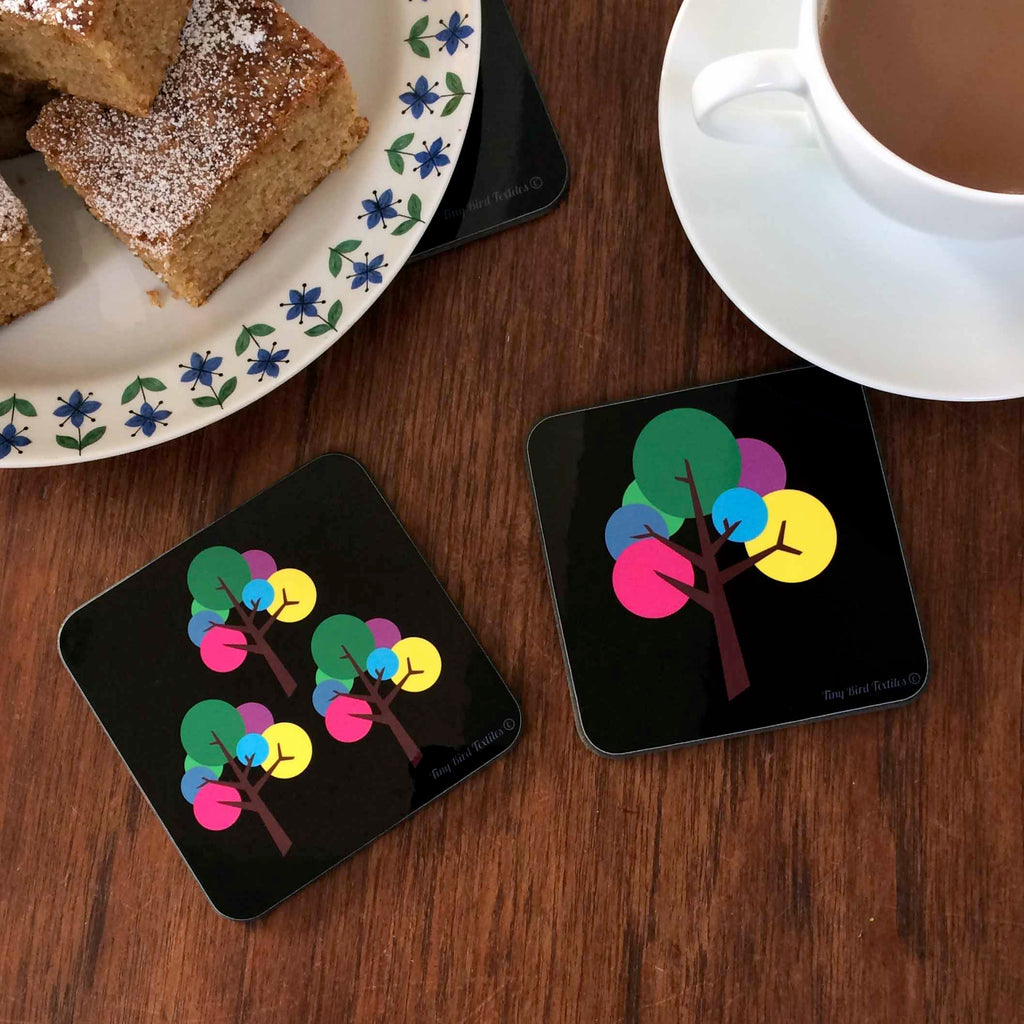 2 Square coaster, drinks mat in black and bright, colourful rainbow pink, purple, blue, yellow, green and grey Oak Tree design; one coaster with a single tree the other with 3 trees, next to a cup of tea and a plate of icing sugar dusted cake squares, on a dark wood table