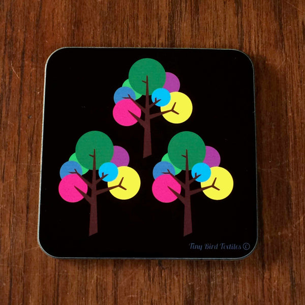 1 Square coaster, drinks mat in black and bright, colourful rainbow pink, purple, blue, yellow, green and grey Oak Tree design; 1 coaster with 3 trees, on a dark wood table