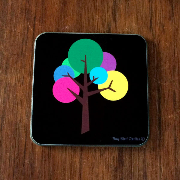 1 Square coaster, drinks mat in black and bright, colourful rainbow pink, purple, blue, yellow, green and grey Oak Tree design; 1 coaster with a single tree on it, on a dark wood table