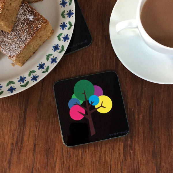 A single square coaster, drinks mat in black and bright, colourful rainbow pink, purple, blue, yellow, green and grey Oak Tree design; one coaster with a single tree, next to a cup of tea and a plate of icing sugar dusted cake squares, on a dark wood table