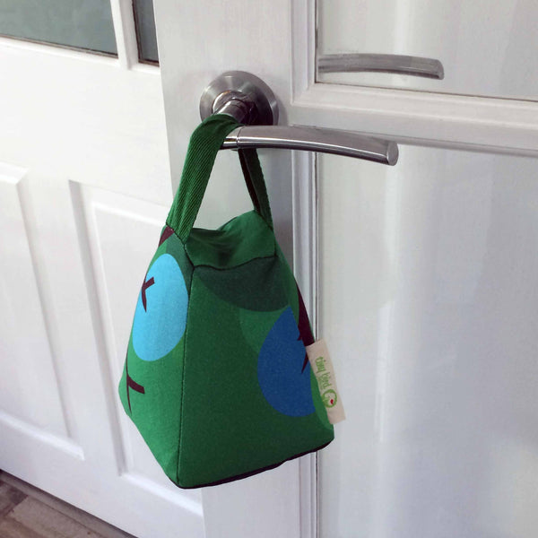 Tapered square door stop in bright green, with green handle and blue and brown design detail handing from a silver door handle