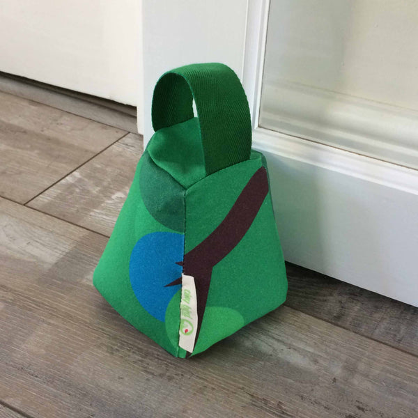 Tapered square door stop in bright green, with green handle and blue and brown design detail resting against a white door on a wooden floor with Tiny Bird Textiles label