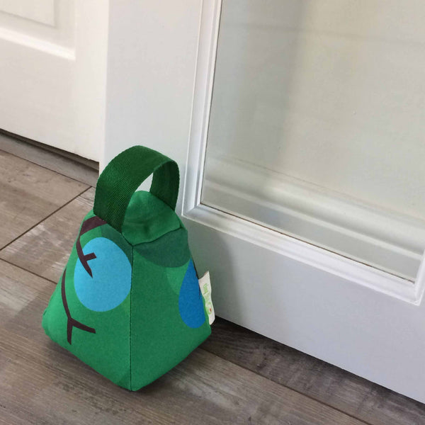 Tapered square door stop in bright green, with green handle and blue and brown design detail resting against a white door on a wooden floor