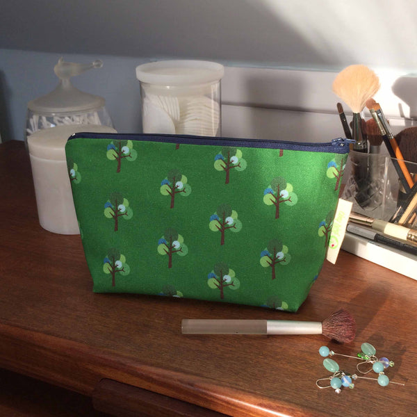 Make up cosmetics bag by Tiny Bird Textiles Oak Tree repeat pattern in green and blue on dark wood dressing table with earrings and make-up brush in the foreground