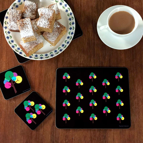 Image of a table setting including 2 Square coaster, drinks mat, 1 placemat in black and bright, colourful rainbow pink, purple, blue, yellow, green and grey Oak Tree design; 1 coaster with 3 trees, placemat with repeated pattern of Oak Trees, with a cup of tea and plate of icing sugar dusted cake squares, on a dark wood table