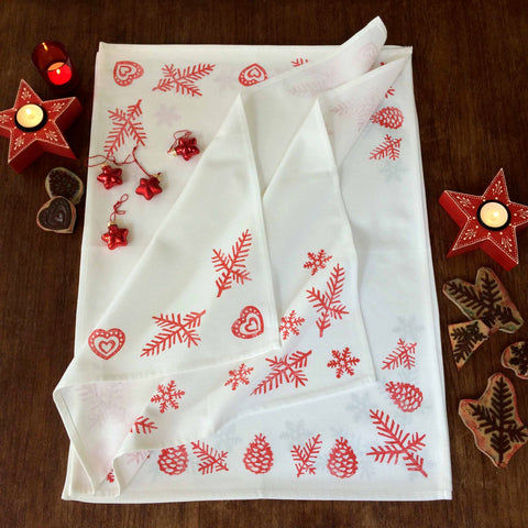 Tiny Bird Textiles Christmas tea towel with red hand lino block printed Scandinavian style snowflake, pine cone and heart design, with lit candles and Christmas decorations and lino blocks