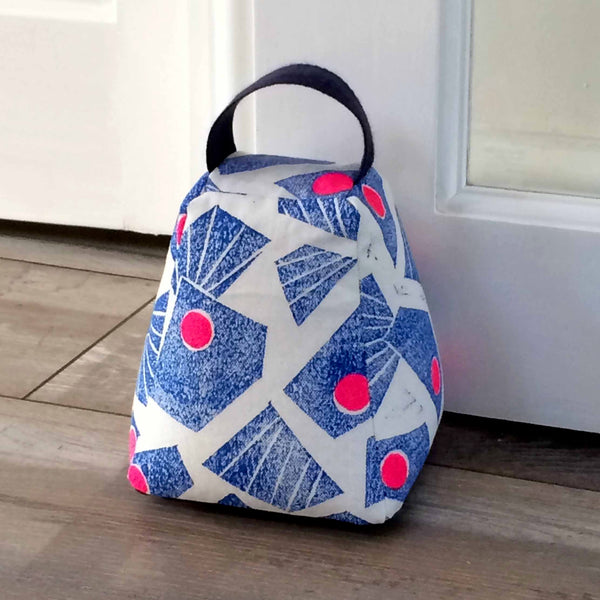 Tiny Bird Textiles Door stop in hand printed bright blue and pink geometric design wood floor in front of a door