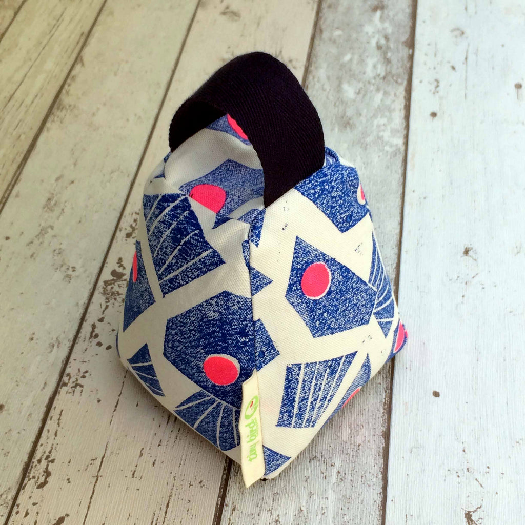 Tiny Bird Textiles Door stop in hand printed bright blue and pink geometric design on bleached wood surface