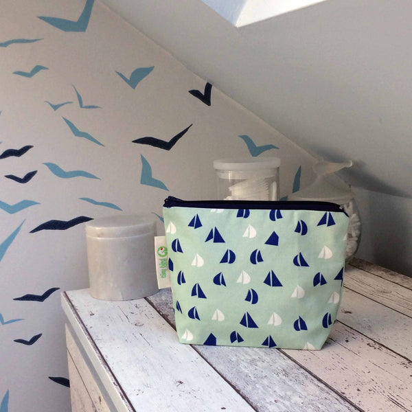 tiny bird textiles rectangle make up bag in sea foam green with blue and white yacht sails on white wood surface with jars of cotton wool in the background