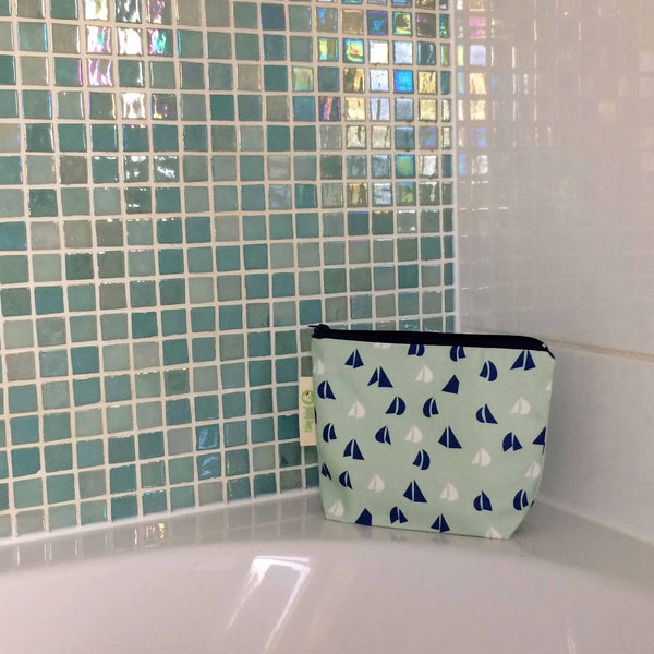 tiny bird textiles close up of rectangle make up bag in sea foam green with blue and white yacht sails on the side of bath with green sparkly tiles and white tiles