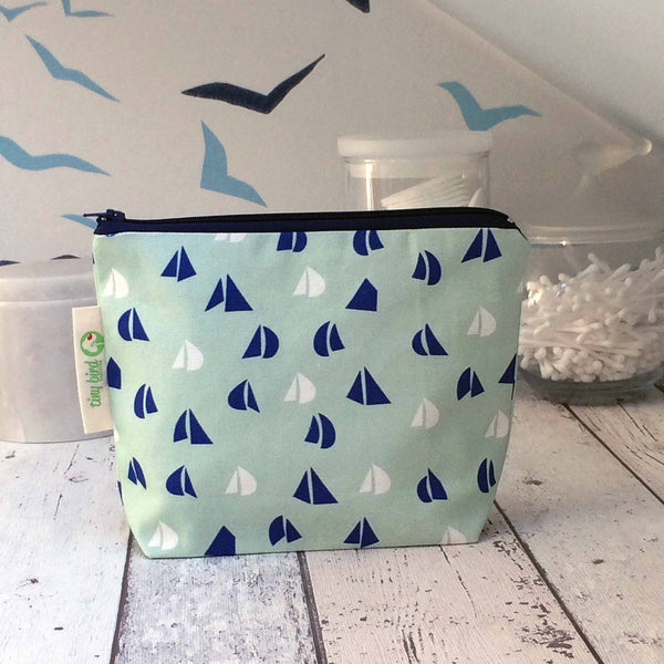 tiny bird textiles close up of rectangle make up bag in sea foam green with blue and white yacht sails on white wood surface with jars of cotton wool in the background