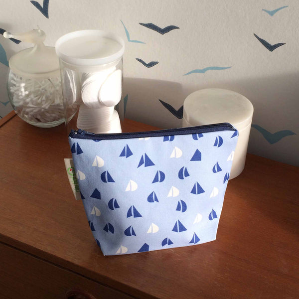 Tiny Bird Textile dark navy blue make up cosmetics bag with light blue and white sail pattern on dark wood dressing table against seagull wallpaper