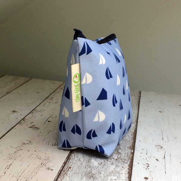 Side view of Tiny Bird Textile dark navy blue make up cosmetics bag with light blue and white sail pattern on bleach wood surface