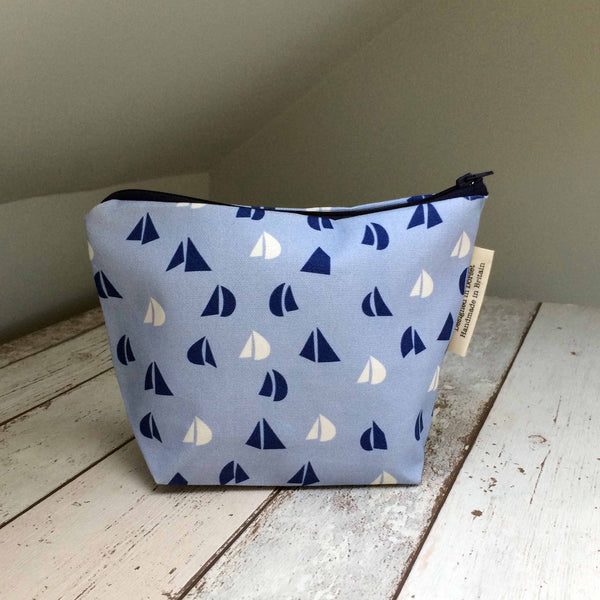 Back view of Tiny Bird Textile dark navy blue make up cosmetics bag with light blue and white sail pattern on bleach wood surface