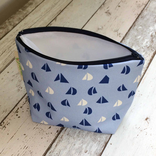 Tiny Bird Textile dark navy blue make up cosmetics bag with light blue and white sail pattern on bleach wood surface with zipper open