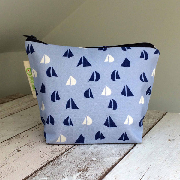 Front view of Tiny Bird Textile dark navy blue make up cosmetics bag with light blue and white sail pattern on bleach wood surface