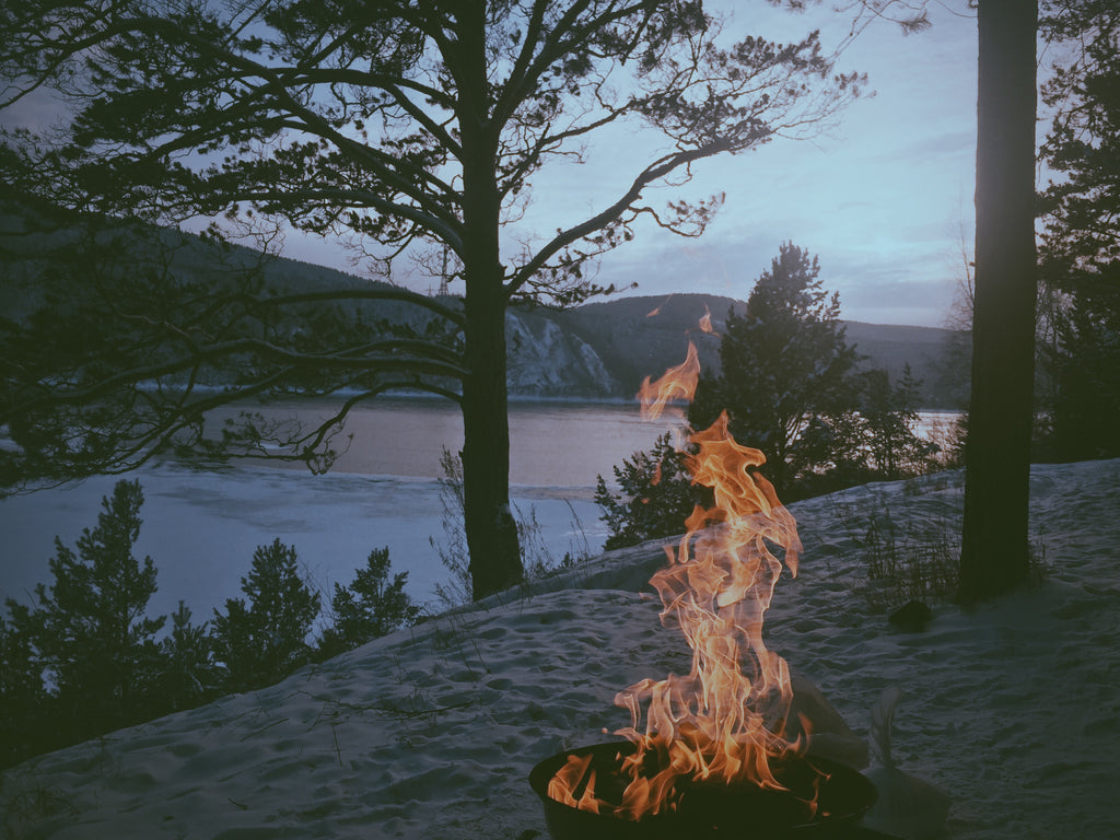 a bonfire out by a lake at night