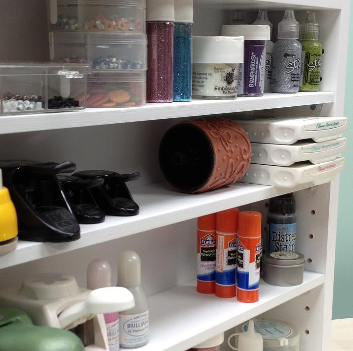 A close up view of the adjustable shelves with craft supplies on it such as glue sticks, stamp pad roller, paper punches, glitter glue, and more.