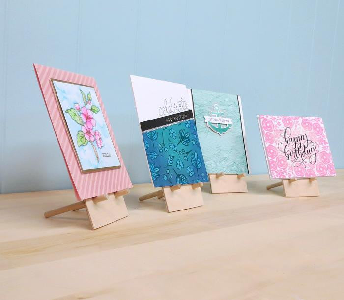 Side view of four card easels displaying cards as if at a craft show.