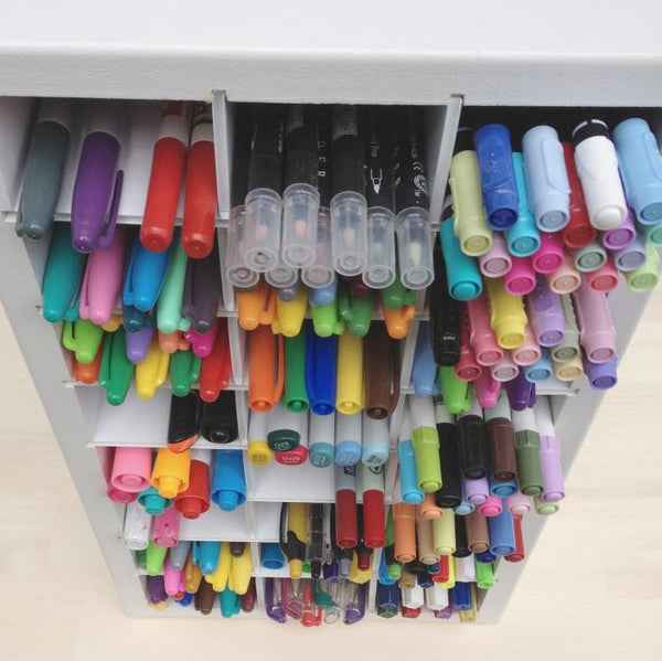 A colorful above view of storage of marker, sharpies, pens, and more in the craft organizer.