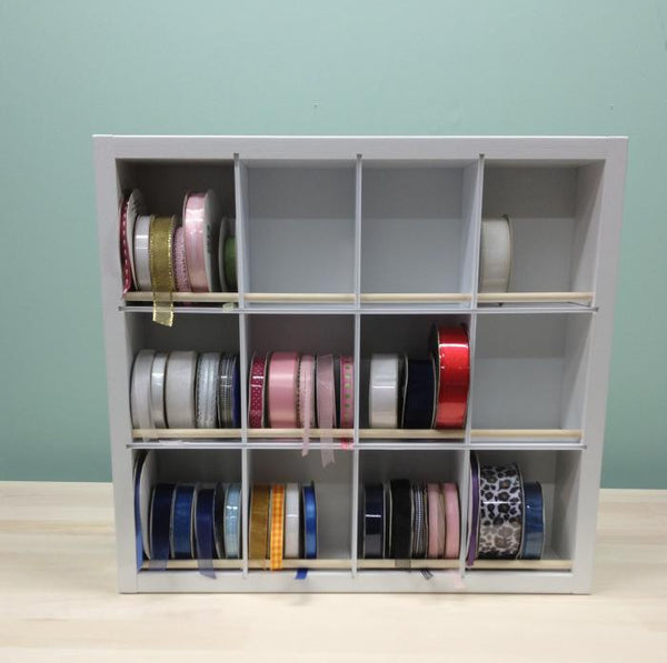 A front view of the Ribbon organizer and some cubbies are filled with ribbon, others empty.