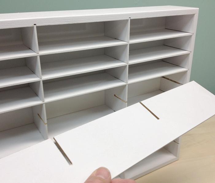 A picture of a hand pulling out the shelves showing that this organizer can be adjusted to fit the type of paper punch.