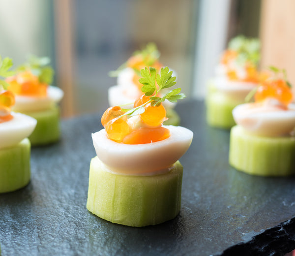 Quail egg and salmon roe on cucumber