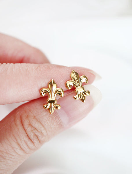gold fleur de lis stud earrings in hand