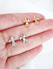 silver and gold fleur de lis earrings in hand