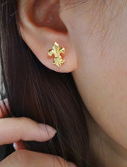 gold fleur de lis stud earrings modelled