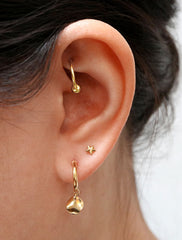 gold hoop earring with wavy coin charm modelled