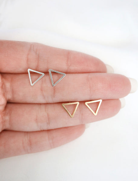 silver and gold open triangle studs in hand