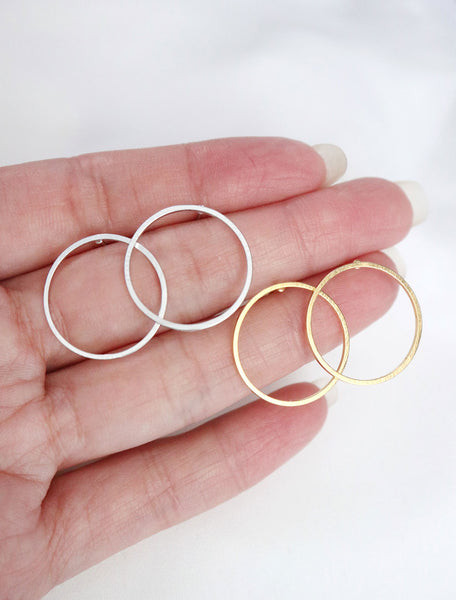 silver and gold circle hoop studs in hand