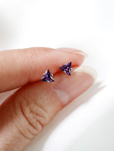 tiny amethyst triangle studs in hand, february birth stone
