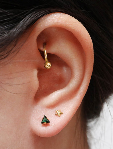 tiny emerald triangle stud earrings modelled, may birthstone