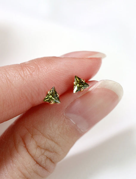 tiny olivine triangle stud earrings in hand, august birthstone